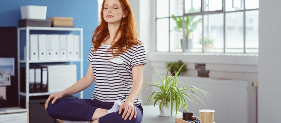 Young woman meditating on her desk at the office | Hubgets